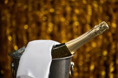 Bottle of champagne in a bucket with ice on the background of golden bokeh