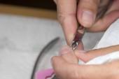 Fotografie Make-up-Einrichtungen. Nahaufnahme der Maniküre anwenden, die Nagelhaut mit einer Schere schneiden. Frau im Nagelstudio Maniküre von professionellen Kosmetikerin empfangen. Maniküre Prozess im Beauty-Salon, Nahaufnahme