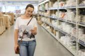 Fényképek Szép nő, vásárlás a szupermarketben, és eldönti, mit kell vásárolni. Vásárlás a szupermarketben, a gyönyörű nő