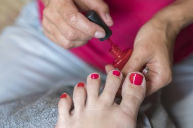 Hands in gloves cares about a woman's foot nails. Pedicure, manicure beauty salon concept. Nail varnishing in red color