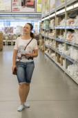 Fényképek Szép nő, vásárlás a szupermarketben, és eldönti, mit kell vásárolni. Gyönyörű nő és vásárlás a szupermarketben. függőleges fénykép