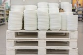 Mnoho desek na polici v obchodě bílé sada vaření. Police v různých bílých desek v úložišti. Kuchyňský porcelán.