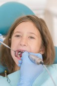 Fotografie Macro close up of young child with open mouth at dentist. Teeth checkup at dentists office. Dentist examining girls teeth in the dentists chair. vertical photo.