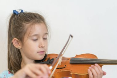 Portrait of a young blond teenage girl playing violin. Girl playing the violin on a light background.