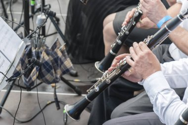 Men play the clarinet in the orchestra. People play on wind instruments.