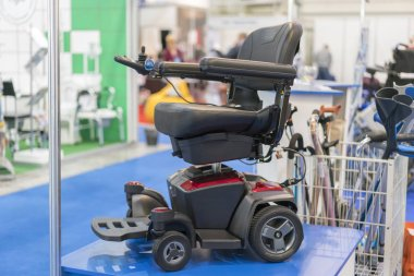 Wheelchair at a medical exhibition. Wheelchair with electric motor