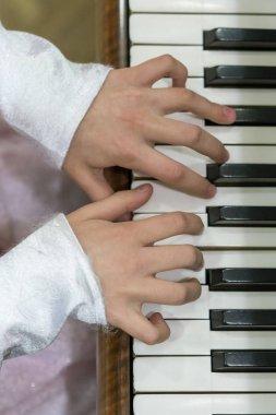 Children's hands on piano keys. vertical photo.