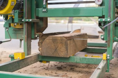 Sawmill. Process of machining logs in equipment sawmill machine saw saws the tree trunk on the plank boards. Wood sawdust work sawing timber wood wooden woodworking.