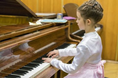little girl playing the grand piano.
