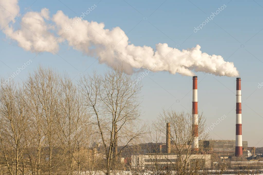 Two large smoking pipes against the blue sky. White thick smoke