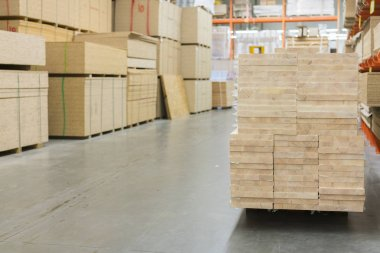 Timber in warehouse. Pallets with boards in hardware store.