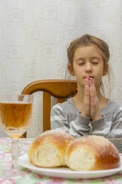 Child prays at Shabbat. Little Jewish Sabbath. Jewish child at the Sabbath table. vertical photo.