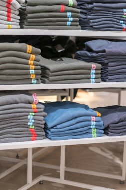 Neatly folded clothes. Rack of clothes with warm. Wooden cabinet with a stack of sweaters. Coloured clothing. Neat stacks of folded clothing on the shop shelves. vertical photo