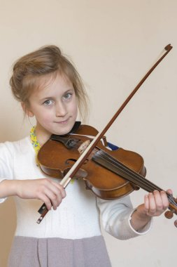 Cute little girl in a beautiful dress playing violin. Joyful and happy emotions. Training. Education. School. Aesthetic training. Portrait of a young girl playing violin on light backgroundl.