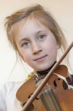 Close up of a child playing violin on isolated light background. Portrait of girl with string and playing violin. Portrait of the little violinist. Beautiful gifted little girl playing on violin