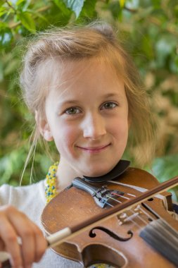 Close up of a child playing violin on green background. Portrait of girl with string and playing violin. Portrait of the little violinist. Beautiful gifted little girl playing on violin.