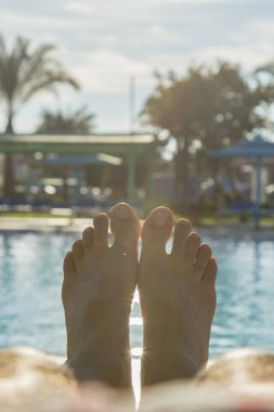 Man's feet on the background of a swimming pool. man relaxing by the pool, men's feet on the pool background. toned. vertical photo.