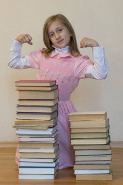 Concept The power of knowledge. Girl with pile of books showig strength. Education concept.