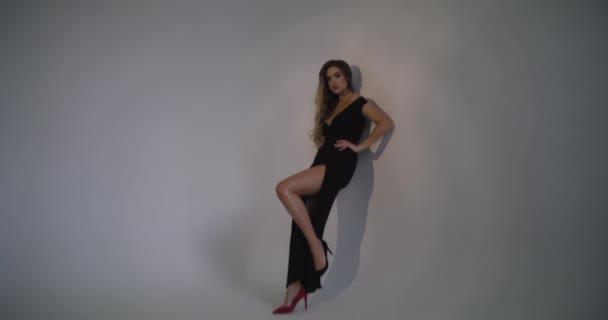 A lány a falnak támaszkodik fekete ruhában. Közeledik a kamera.