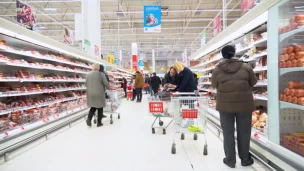 Lidé s nákupními vozíky v zimních bundách volí a kupují produkty v klobáse na hypertržišti v Auchanu. Police s klobásou.