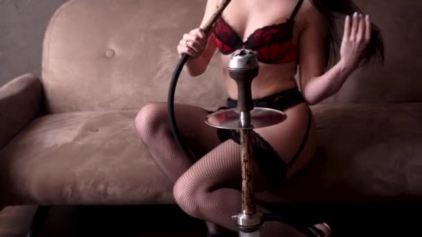 A married sexy woman in a beautiful red lace lingerie and stockings with black hair on her heels on a brown sofa at home with the pleasure of smoking a beige wooden hookah. Smoke from mouth.