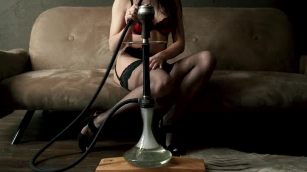 Luxusní sexy žena v nádherné červené krajkové spodní prádlo a punčochy s černými vlasy na vysokých podpatcích sedí na hnědé pohovce na dřevěné podlaze. Mladá dívka s potěšením kouří matný Hookah. Kouř z úst.
