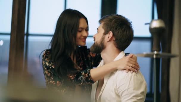 bärtige kaukasische Mann in einem weißen Hemd und eine verheiratete sexy Frau mit langen schwarzen Haaren in schönen roten Spitzenunterwäsche in einem Seidenmantel küsst zu Hause auf dem Hintergrund der kalten Fenster