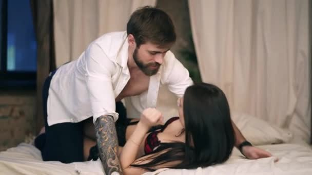 Brutal Caucasian man with short brown hair in a white rumpled shirt looks at an attractive girl in red lace lingerie with long black hair on a beige wooden bed in the bedroom. Male on top of woman.