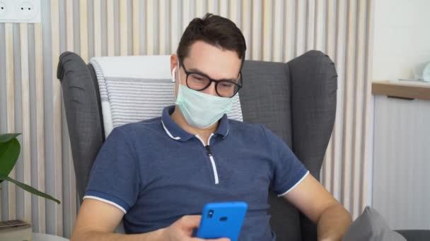 Glücklicher junger Mann mit medizinischer Gesichtsmaske, schwarzer Brille, weißen drahtlosen Kopfhörern, sitzt in einem bequemen weichen Stuhl im Zimmer. Zufriedener Kerl hält Telefon in den Händen. Männer entspannen sich, hören Musik. Glückseligkeit im Gesicht.