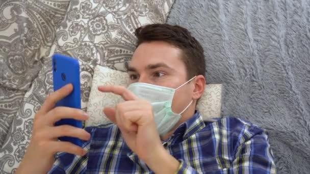 Junge hübsche brünette Mann liegt auf grauem Bett mit blau kariertem Hemd, türkisfarbener Einweg-Mundschutz, hält blaues Telefon in der Hand, blättert Social Feed aus nächster Nähe Ansicht. Sperrung