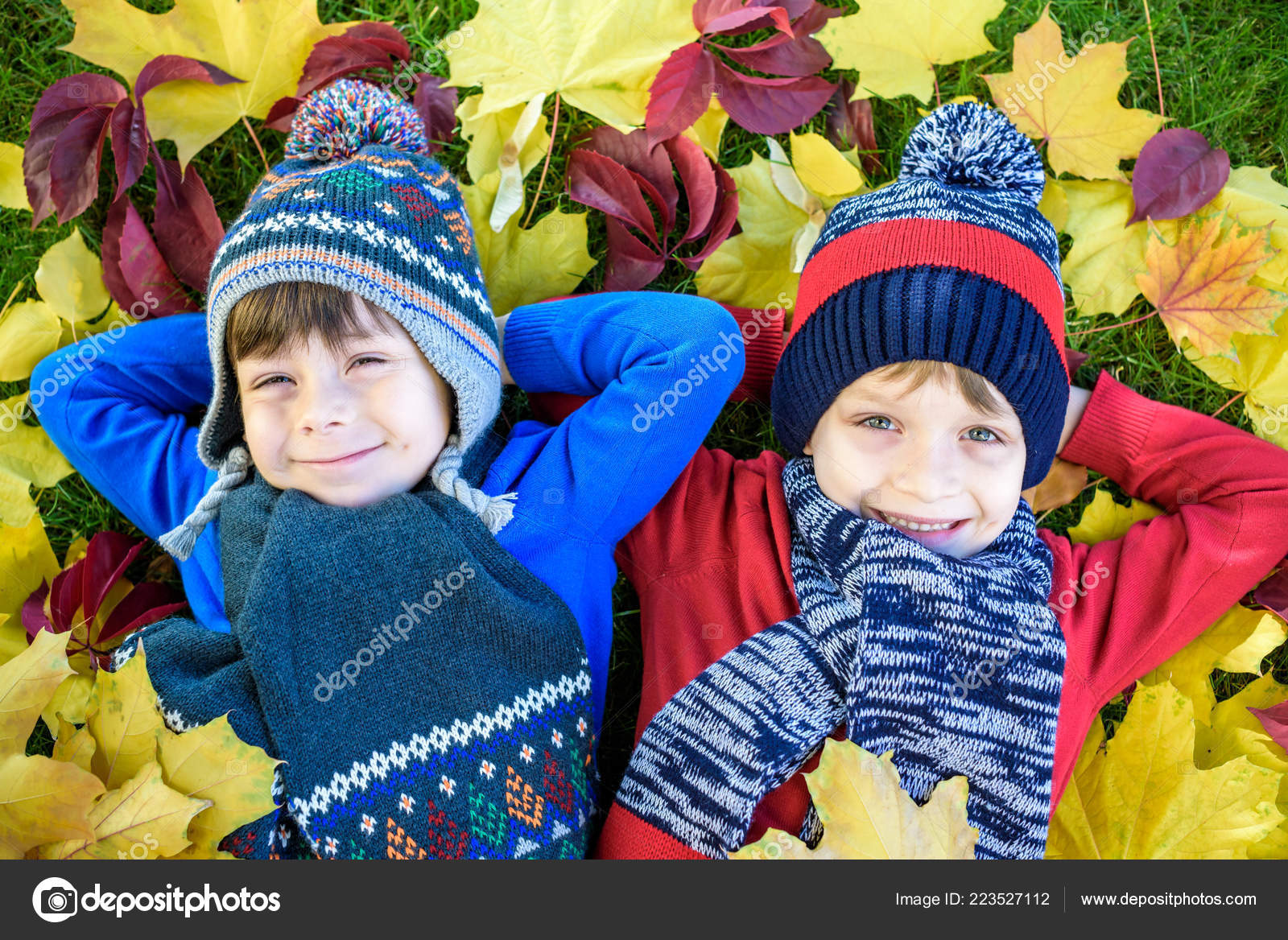525830e5736 Happy siblings having fun in autumn park on warm day. Healthy children  scarf and hat with maple foliage.
