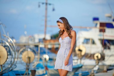A very beautiful sensual and sexy girl in a blue striped dress is walking on the background of yachts and the sea in summer