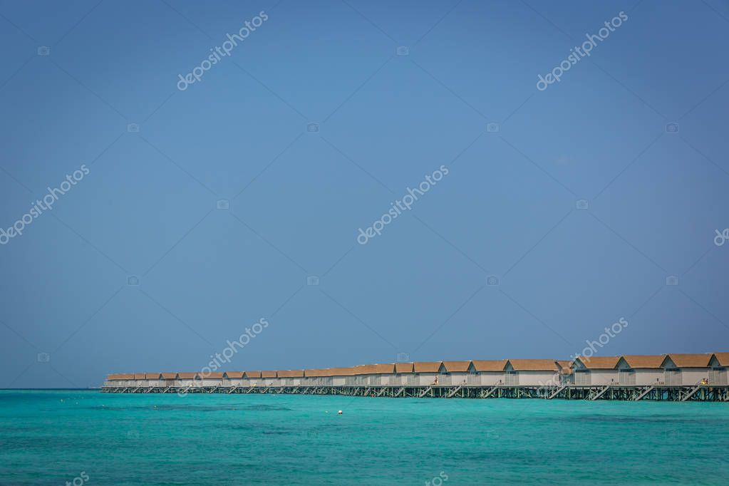 Plenty of bungalows over the blue water of Maldives in a clear sky day