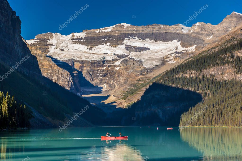 Banff, Canada - Ago 19th 2017 - Tourists doing kayak and enjoying the amazing scenario of lake Moraine, early morning light, glacial at the background, blue sky in summer time Banff.