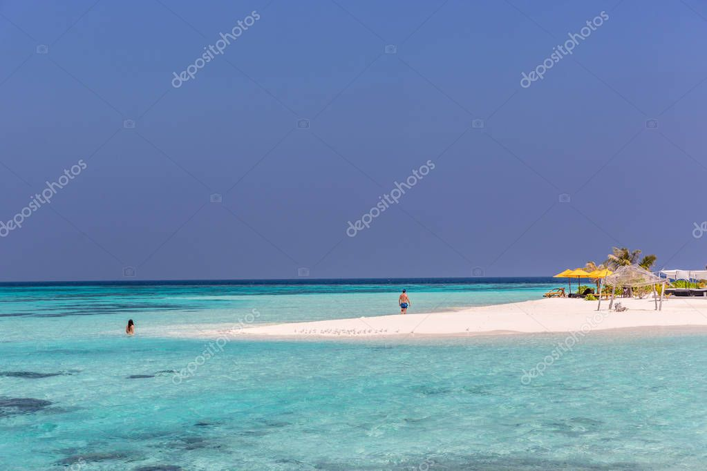 Maldives, Feb 8th 2018 - Tourists swimming in a turquoise blue sea, desert island, small traditional hut hotel on a blue sky day, paradise feeling in Maldives.