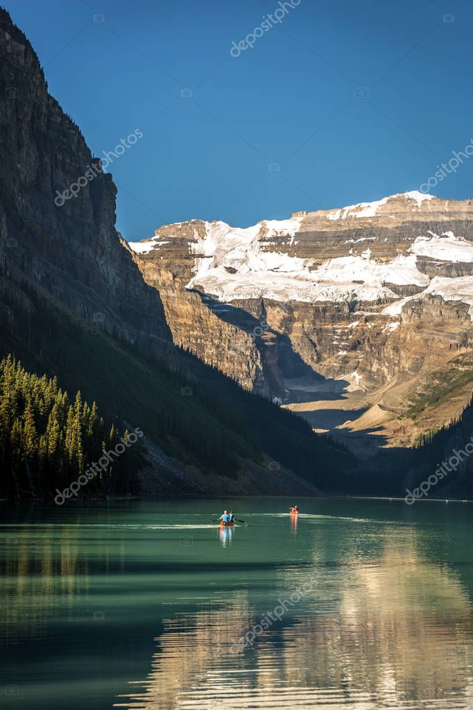 Amazing lake surrounded by mountains and glaciers, tourists doing kayak in a blue sky day in Banff National Park in Canada