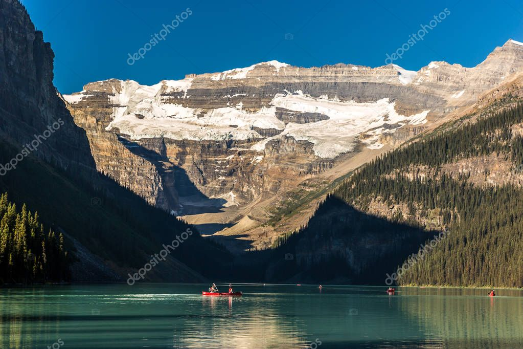 Green lake surrounded by mountains and glaciers, tourists doing kayak in a blue sky day in Banff National Park in Canada