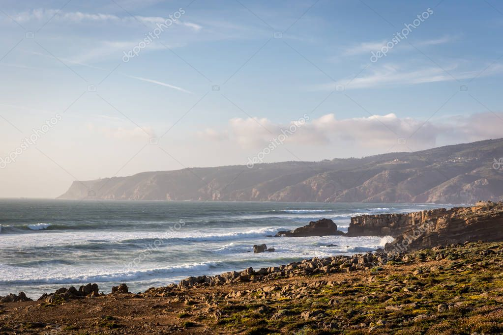 Amazing landscape scenario at the Guincho beach in Cascais, Portugal. Sunset colors, mountains, big waves.
