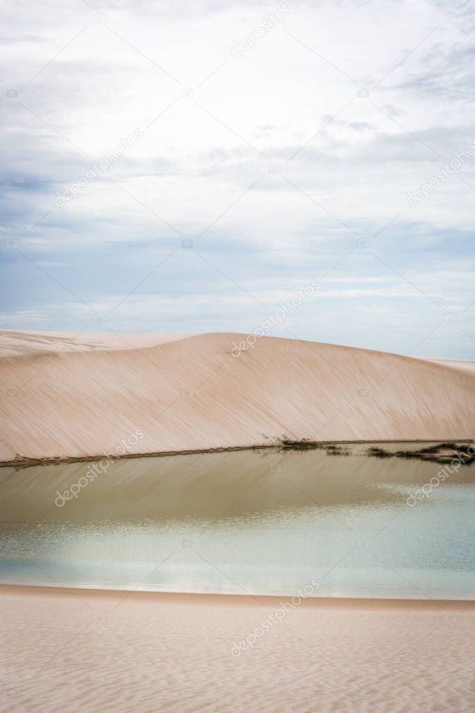 Amazing white sand dunes with natural pool lagoons in the middle of it, cloudy day. Reflection in the water.