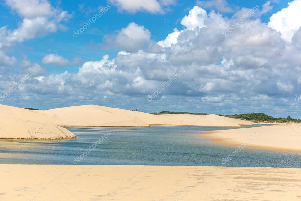 Freshwater lagoons in the middle of a white sand desert, clouds in the sky with green trees in the background