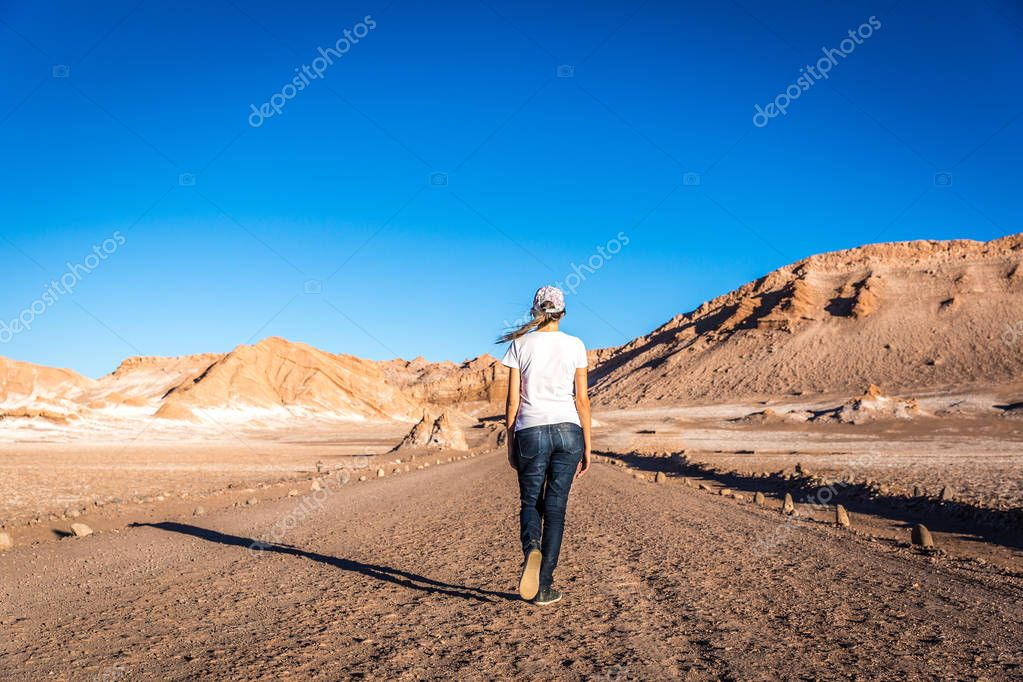Woman in a jeans walking in the middle of the road in a stunning landscape in the Moon valley (valle de la luna) in Atacama Desert, Chile