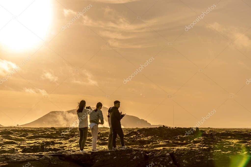 Iceland, Reykjavik - Oct 24th 2017 - Tourists enjoying the unique landscape of Reykjavik, sun straight in the image, light marks, warm colors.
