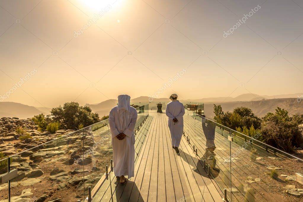 Two mans dressing with arab white clothes in a hotel in Oman. Orange predominance in the picture, feeling of desert, dry place, no clouds