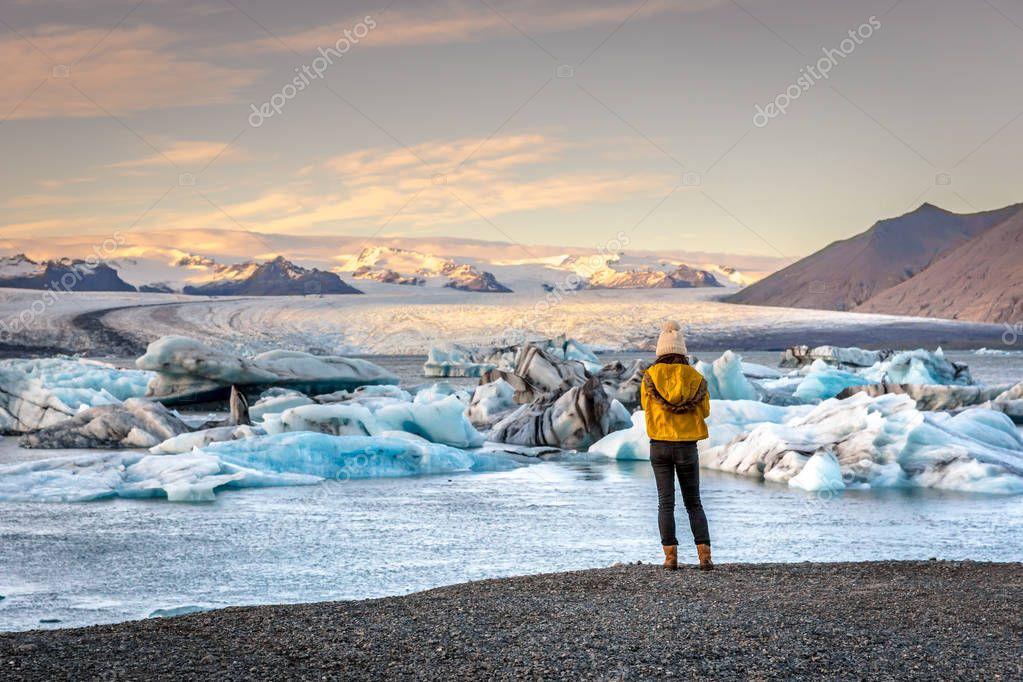 Young woman dressing cold clothes seeing the amazing Jokulsarlon, iceberg lagoon in Iceland
