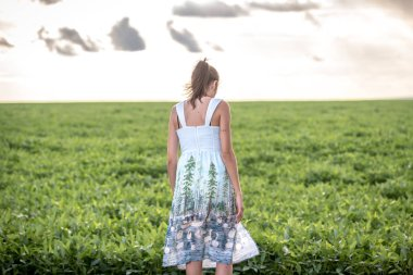 Woman dressed casual in front of a large soybean plantation in Brazil
