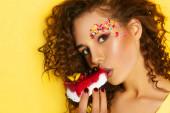Sexy Frau mit kreativem Mode-Make-up und Frisur hält leckeren Kuchen in der Hand und blickt voller Lust auf Essen in die Kamera. Süßigkeiten essen. Sinnlicher Blick. Vor leuchtend gelbem Hintergrund. Helles Make-up und Lippenstift. Sehnsucht. Schönheit Mädchen Sexy Lippen mit Erdbeere