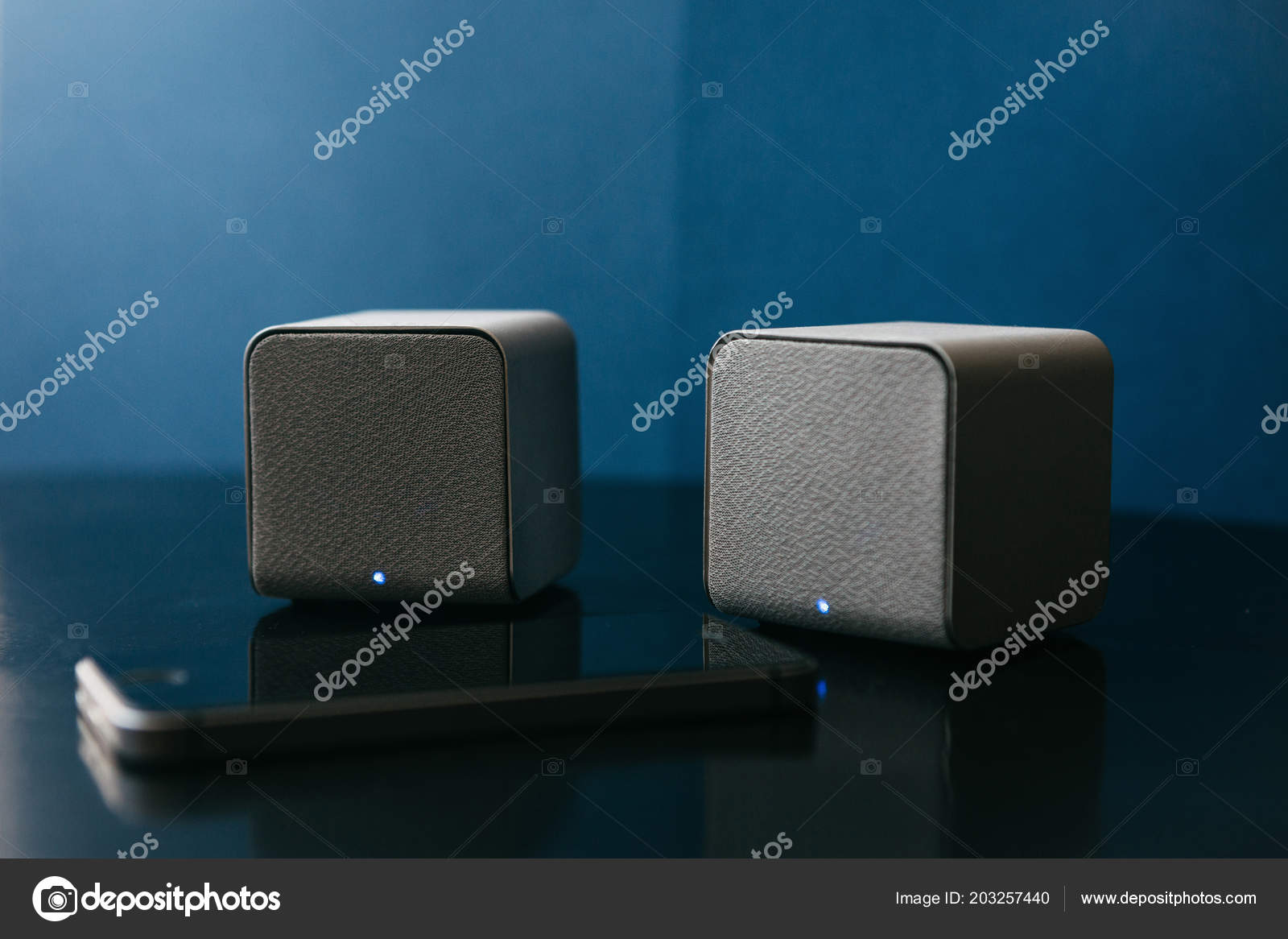 Wireless speakers and a cell phone next to them on a dark