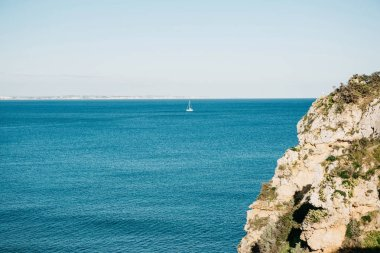 A view of the Atlantic Ocean and a sailboat floating in the distance.