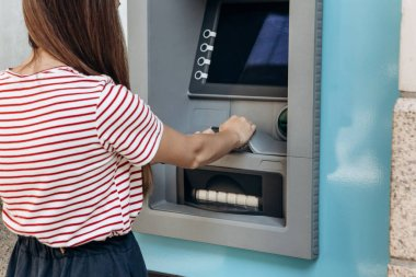 A young woman takes money from an ATM. Grabs a card from the ATM. Finance, credit card, withdrawal of money.