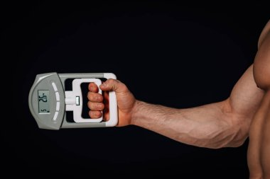 Sporty man holding hand's dynamometer at black background